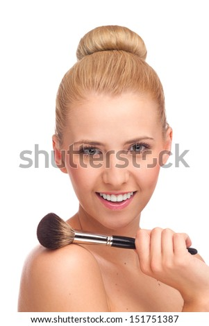 Happy young blond woman with make-up brush on shoulder looking at camera. Beauty shot isolated on white. - stock photo