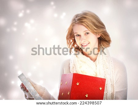 Happy young blonde woman holding many gift boxes - stock photo