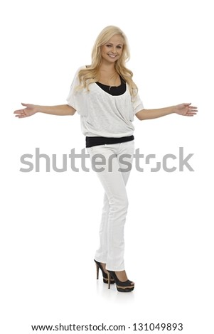Happy young blonde woman standing with arms wide open, full size. - stock photo