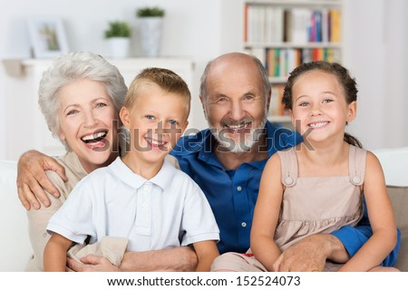 Happy young boy and girl with their laughing grandparents smiling at the camera as they pose together indoors - stock photo