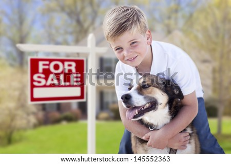 Happy Young Boy and His Dog in Front of For Sale Real Estate Sign and House. - stock photo