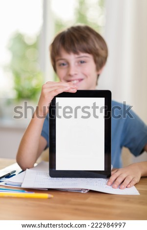 Happy young boy displaying his tablet computer with a blank white screen to the viewer as he sits at a table at home - stock photo