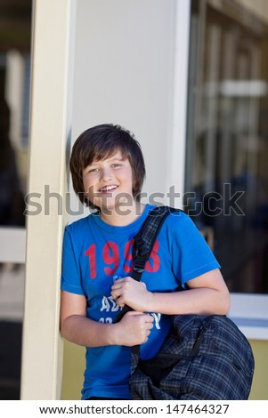 Happy young boy going to school with a large bag of books slung over his shoulder grinning at the camera - stock photo