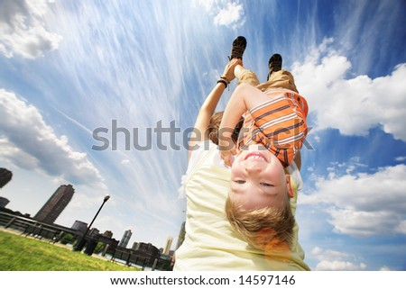 Happy young boy hanging upside down on mother's back over blue sky. - stock photo