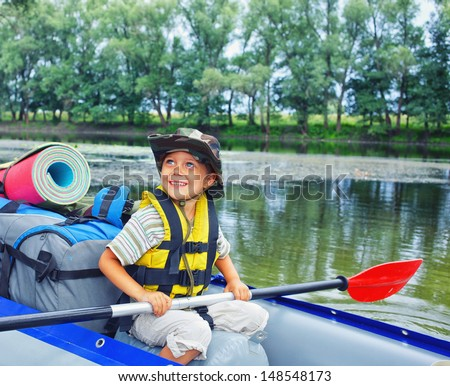 Happy young boy holding paddle near a kayak on the river, enjoying a lovely summer day - stock photo