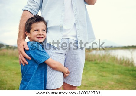 Happy young boy hugging his dad and smiling in the park - stock photo