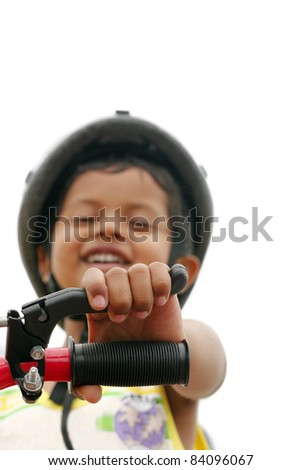 Happy young boy looking on as he rides a cycle - stock photo