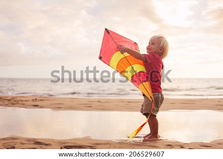 Happy young boy playing with kite on the beach at sunset - stock photo