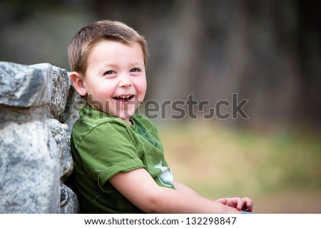 Happy young boy sitting outdoors laughing - stock photo