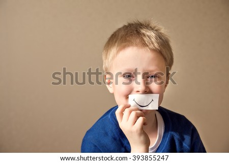 Happy young boy (teen) with paper smile select right positive expressions  - stock photo