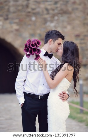 Happy young bride and groom kissing on their wedding day - stock photo
