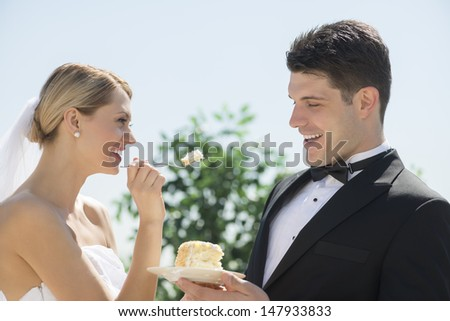 Happy young bride feeding wedding cake to groom outdoors - stock photo