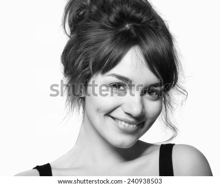Happy young brunette girl with natural makeup smiling with toothy smile in studio environment. Isoalted on white background, copy space - stock photo