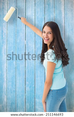 Happy young brunette painting with roller against wooden planks - stock photo