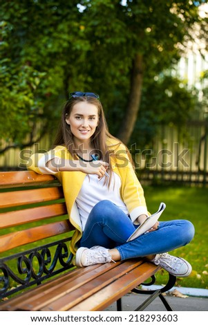 Happy young brunette sitting on a park bench - stock photo
