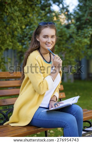 Happy young brunette with a notebook in hands sitting on a park bench  - stock photo
