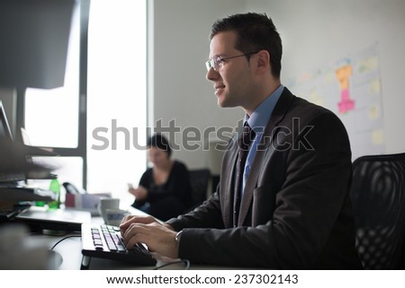 Happy young business man work in modern office on computer.Handsome businessman working with computer in office. Real economist bussinesmen, not a model. Bank offices - stock photo