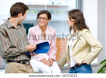 Happy young business people having meeting and reading documents, smiling. - stock photo
