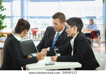 Happy young business people talking on meeting at coffee table, smiling. - stock photo
