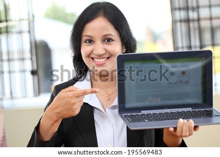 Happy young business woman showing tablet computer - stock photo