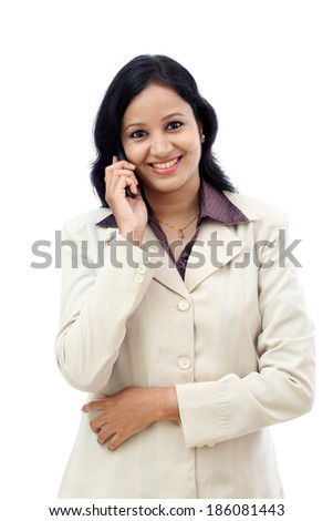 Happy young business woman talking on cell phone against white background - stock photo
