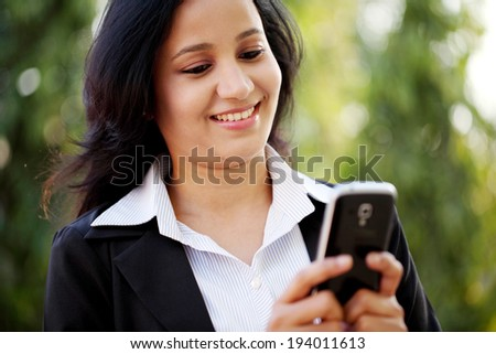 Happy young business woman text messaging at outdoors - stock photo