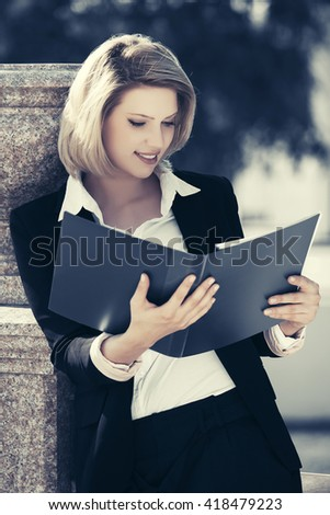 Happy young business woman with a folder outdoor - stock photo