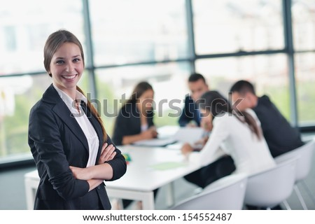 happy young business woman  with her staff,  people group in background at modern bright office indoors - stock photo