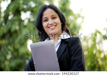 Happy young business woman with tablet computer at outdoors - stock photo