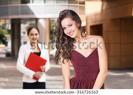 Happy young business women with a folder at the office building - stock photo