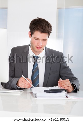 Happy Young Businessman Calculating Bills At Desk - stock photo