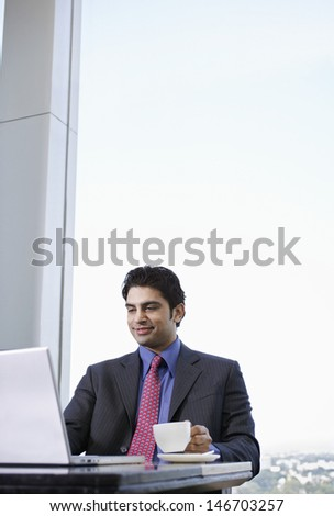 Happy young businessman having tea while using laptop at cafe - stock photo