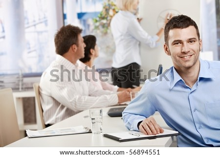 Happy young businessman in business meeting at office, looking at camera smiling.? - stock photo