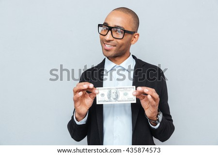 Happy young businessman in glasses smiling and holding dollar banknote - stock photo