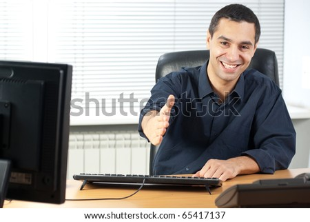 Happy young businessman in his office ready to seal a deal - stock photo