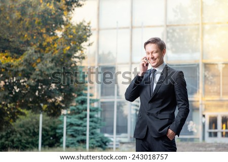 Happy young businessman in suit and tie talking on the mobile phone while standing outdoors with office building in the background - stock photo