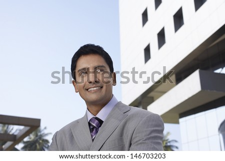 Happy young businessman looking away in front of office building - stock photo
