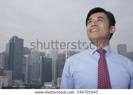 Happy young businessman looking up with cityscape in background - stock photo