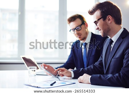 Happy young businessman pointing at touchscreen while explaining data to his colleague - stock photo