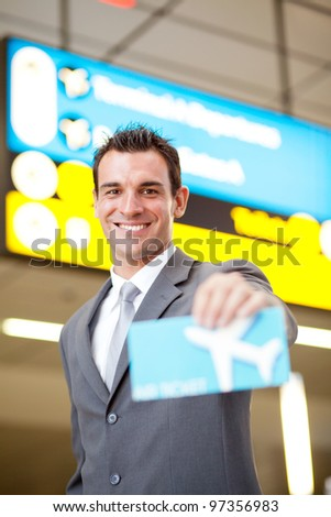 happy young businessman presenting air ticket - stock photo