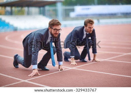 Happy young businessman ready to run on stadium - stock photo