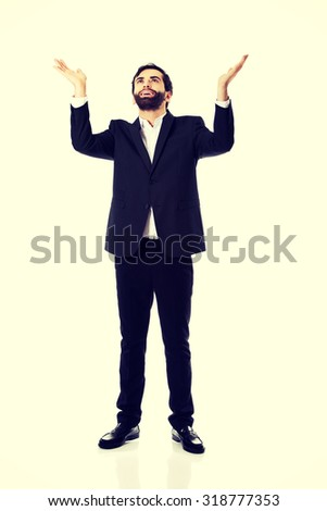 Happy young businessman showing empty copyspace on hands. - stock photo