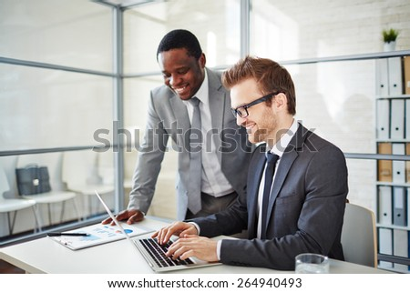 Happy young businessman typing on laptop at workplace with his colleague standing near by - stock photo