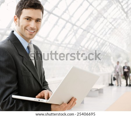 Happy young businessman using laptop in business building, smiling. - stock photo