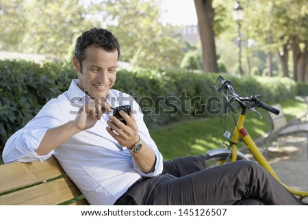 Happy young businessman using palmtop pilot while sitting on park bench - stock photo
