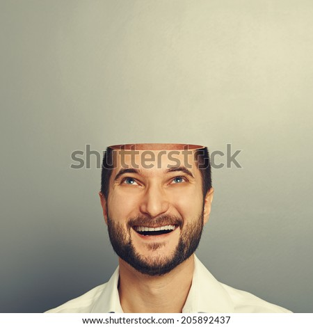 happy young businessman with open head looking up and smiling over grey background - stock photo