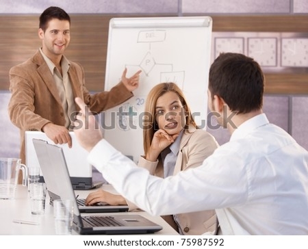 Happy young businesspeople having business training in meeting room.? - stock photo