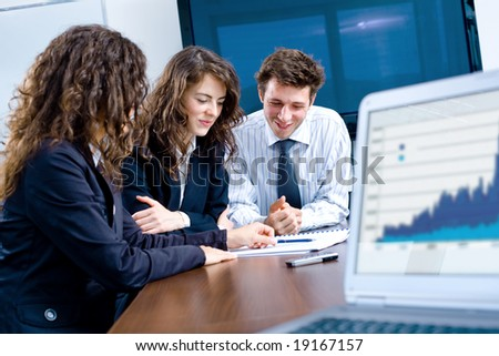 Happy young businesspeople having meeting in board room. Graph showing progress on laptop screen. - stock photo