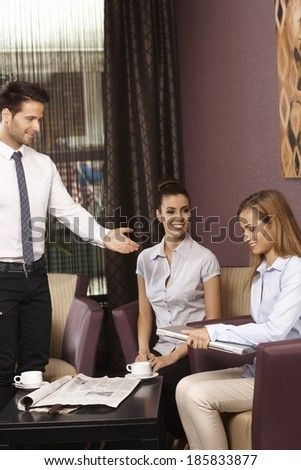 Happy young businesspeople meeting at coffee bar, having laptop computer. - stock photo