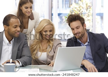 Happy young businessteam working together in office, using laptop computer. - stock photo